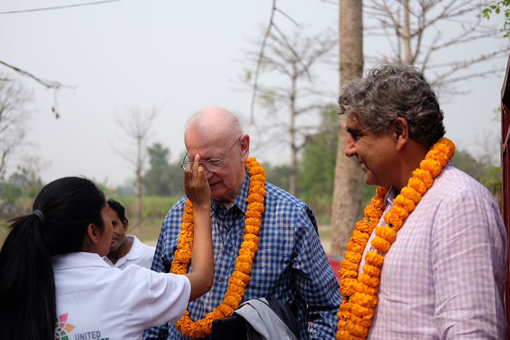 Ray Larsen and Fahrid Kahn are welcomed by villagers